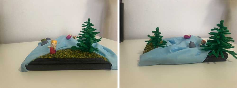 A miniature model of a river running through trees with a person standing next to the river.