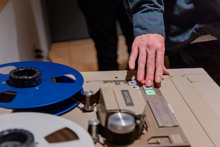 A student uses the 16-track tape machine during Analog Recording class.