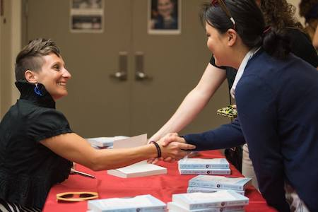 Annie Liontas shakes hands with Creative Writing students over a table of books during the Visiting Writers Series.