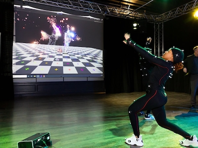 A student tests out motion-capture technology with projections.