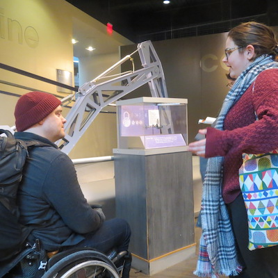A student speaks with workshop leader Ben Baker about accessibility in the Franklin Institute.