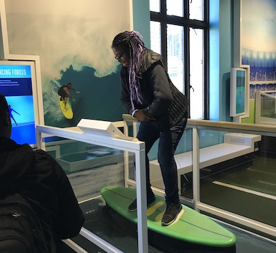 A student tests out an interactive surfing exhibit at the Franklin Institute.