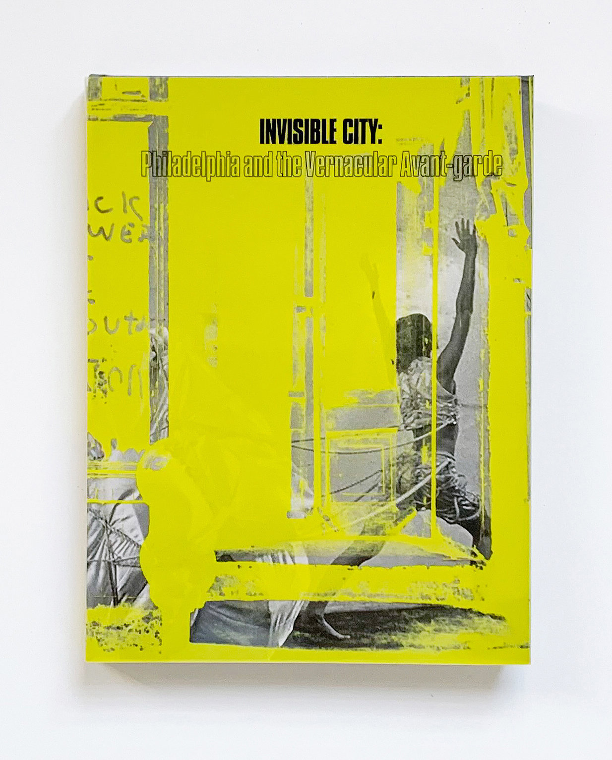 Invisible City catalog cover with neon yellow overlay