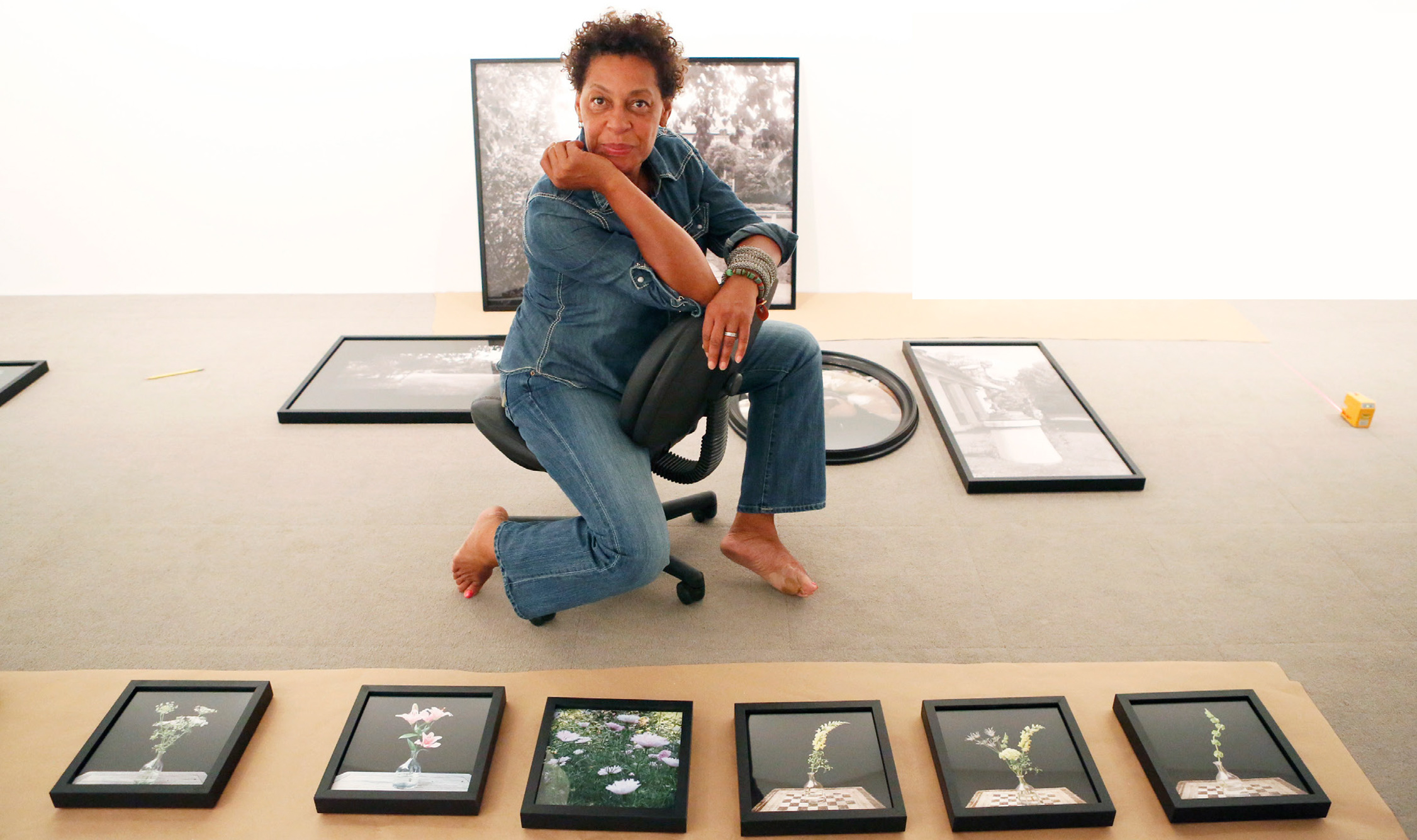 An image of Carrie Mae Weems kneeling in front of her work in black frames.