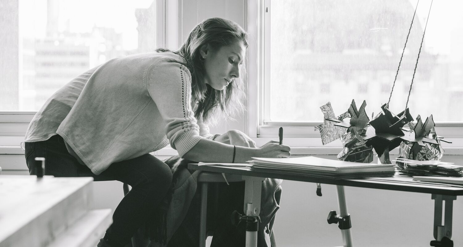A woman sitting at a table, writing; a cardboard and collage sculpture is on the table.