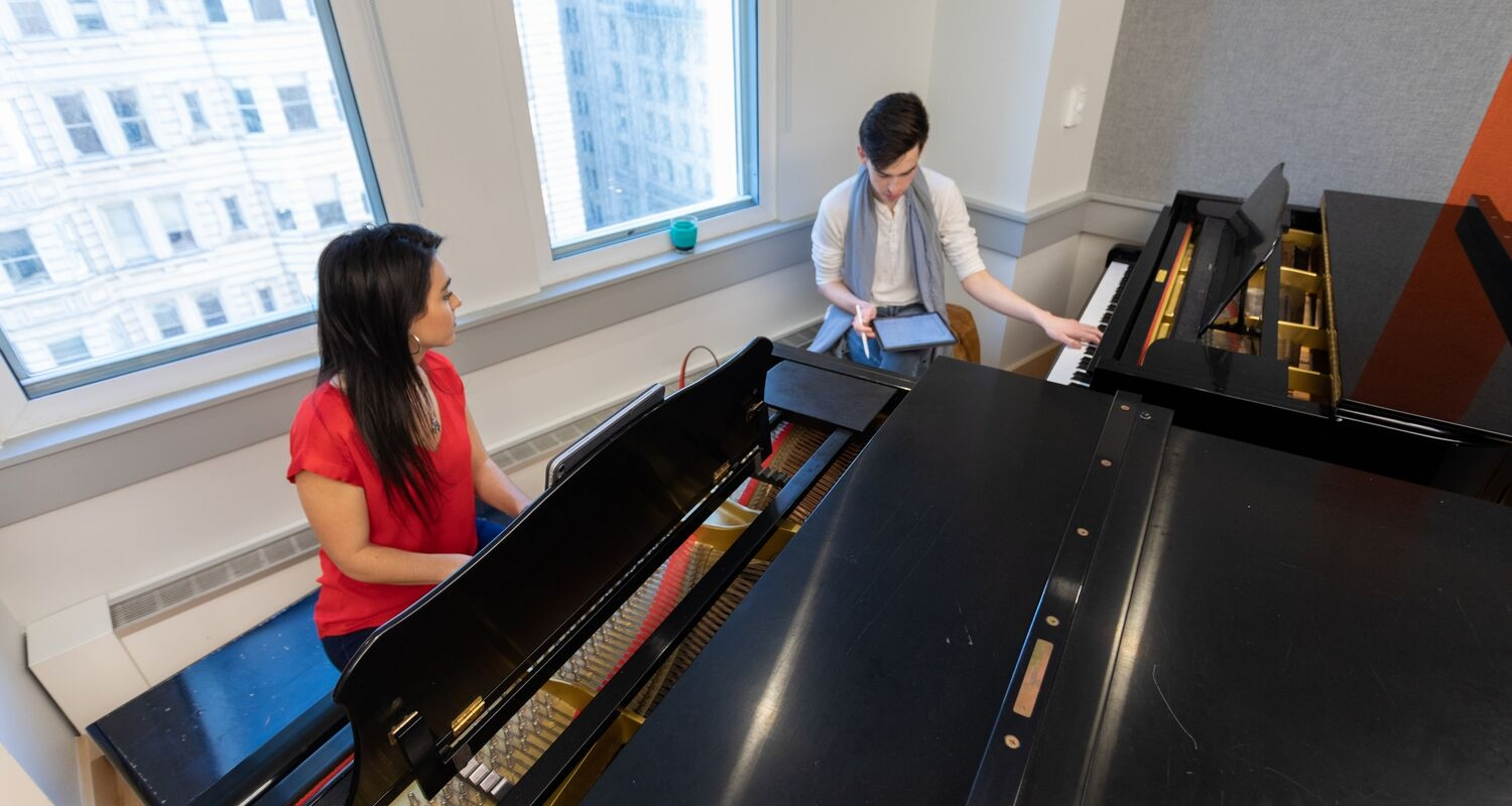UArts student plays at a piano with a professor AJ Luca