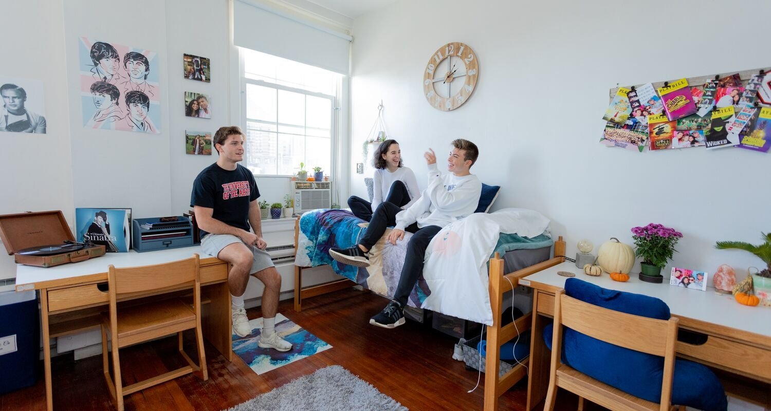 Three students hang out in Spruce residence hall.