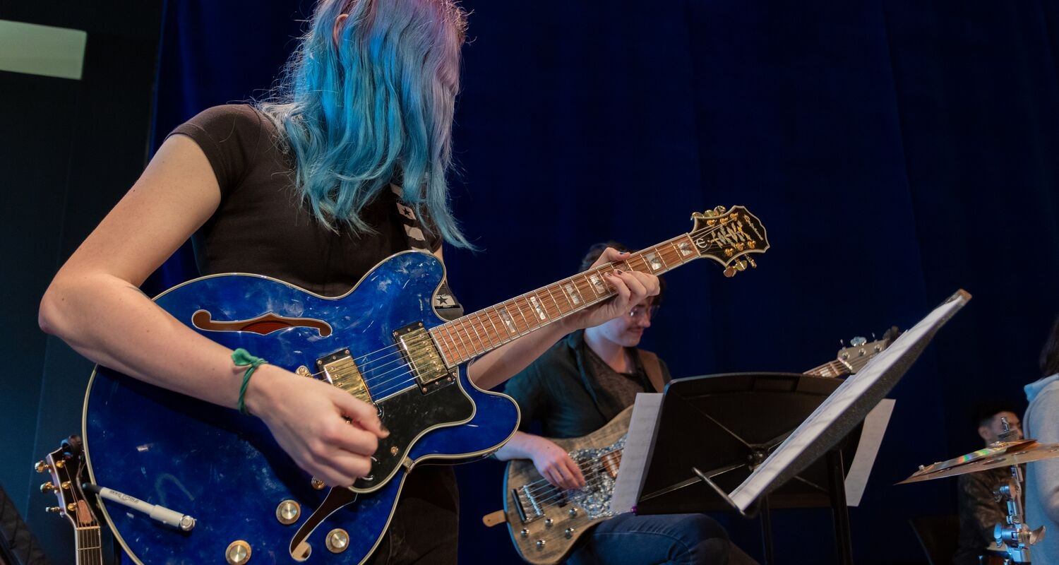 UArts student playing a blue guitar in an ensemble