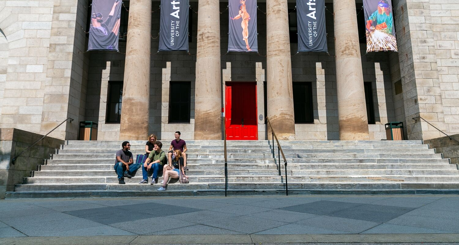 Five students sit on the steps outside Hamilton Hall