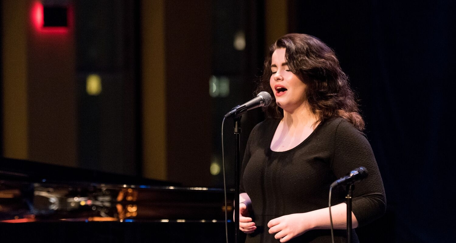 UArts student performs on stage with a mic and piano