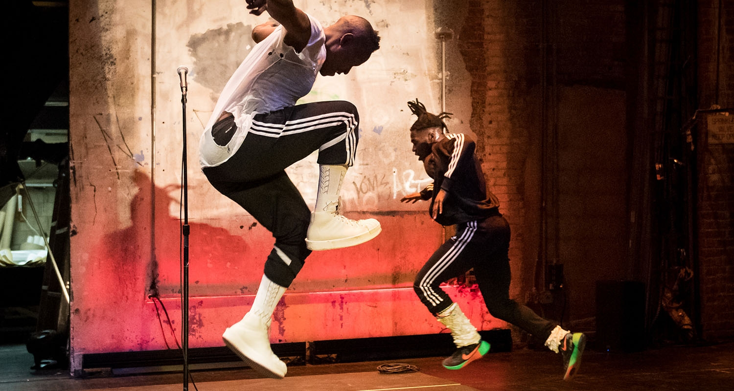Two male dancers in streetwear, both jumping in the air.