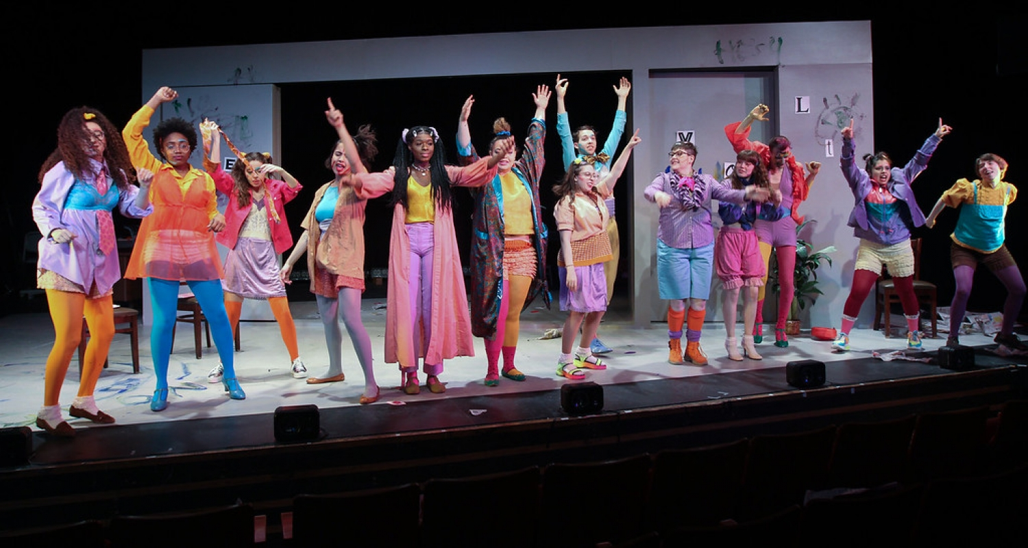 theater students on stage wearing neon colored costumes and make-up