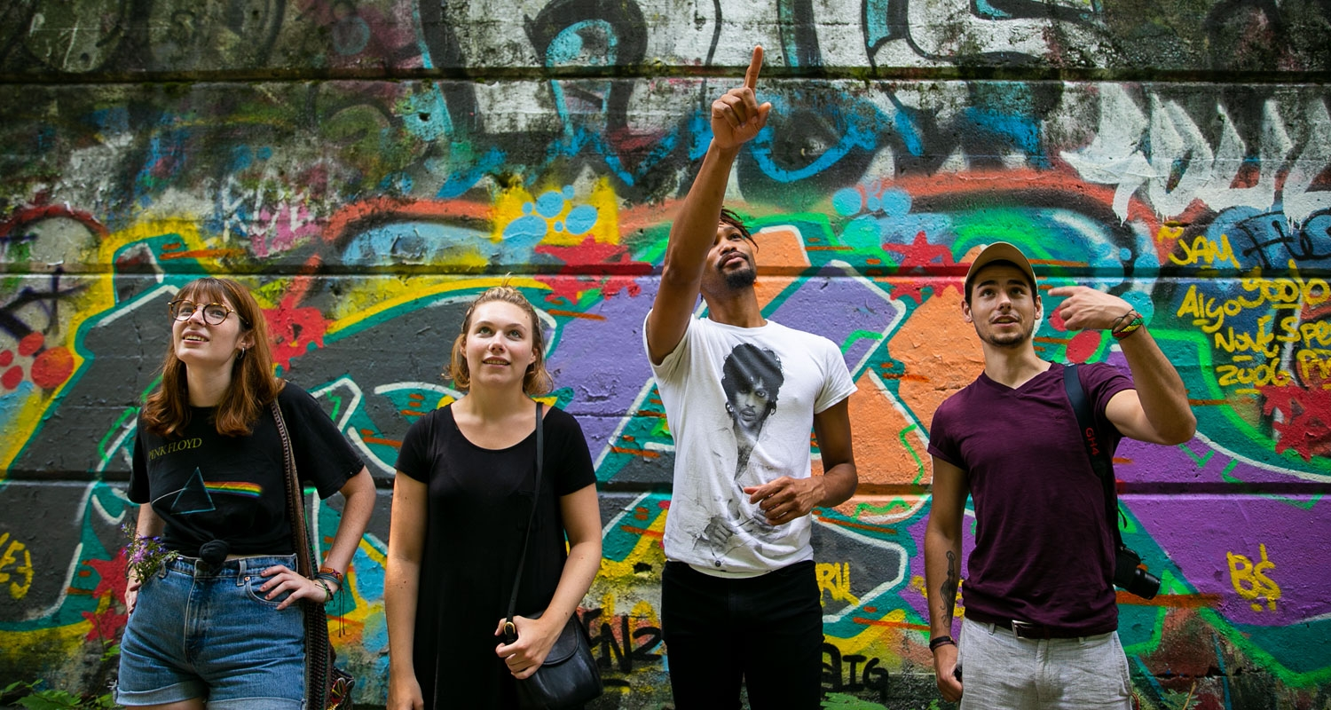 UArts students stand in front of a graffiti background experiencing life in Philadelphia