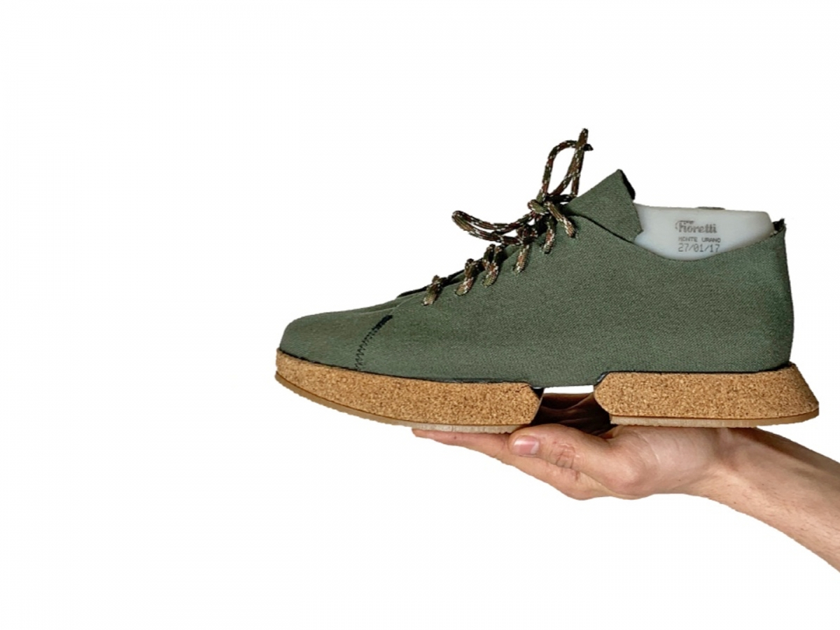 A green pair of sneakers with cork soles over a white background