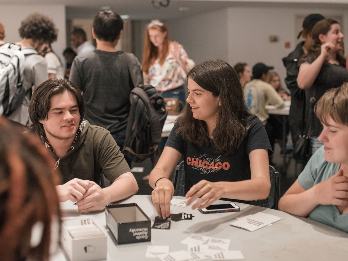 A group of students play a card game during Game Night
