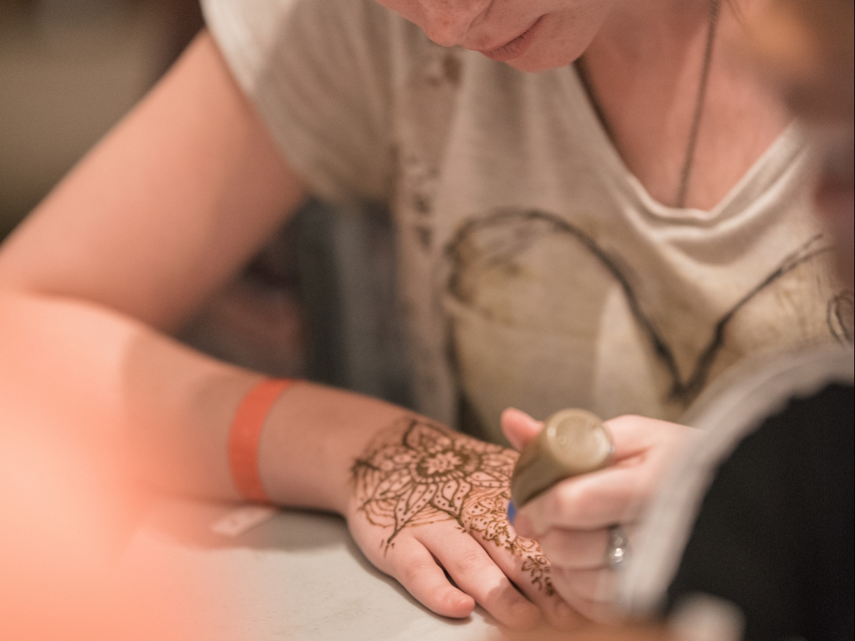 A student concentrates on creating henna art during Henna Night