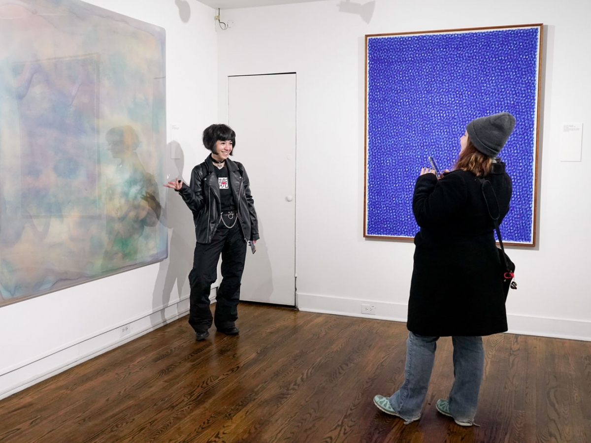 A person posing in front of a painting in the Invisible City gallery