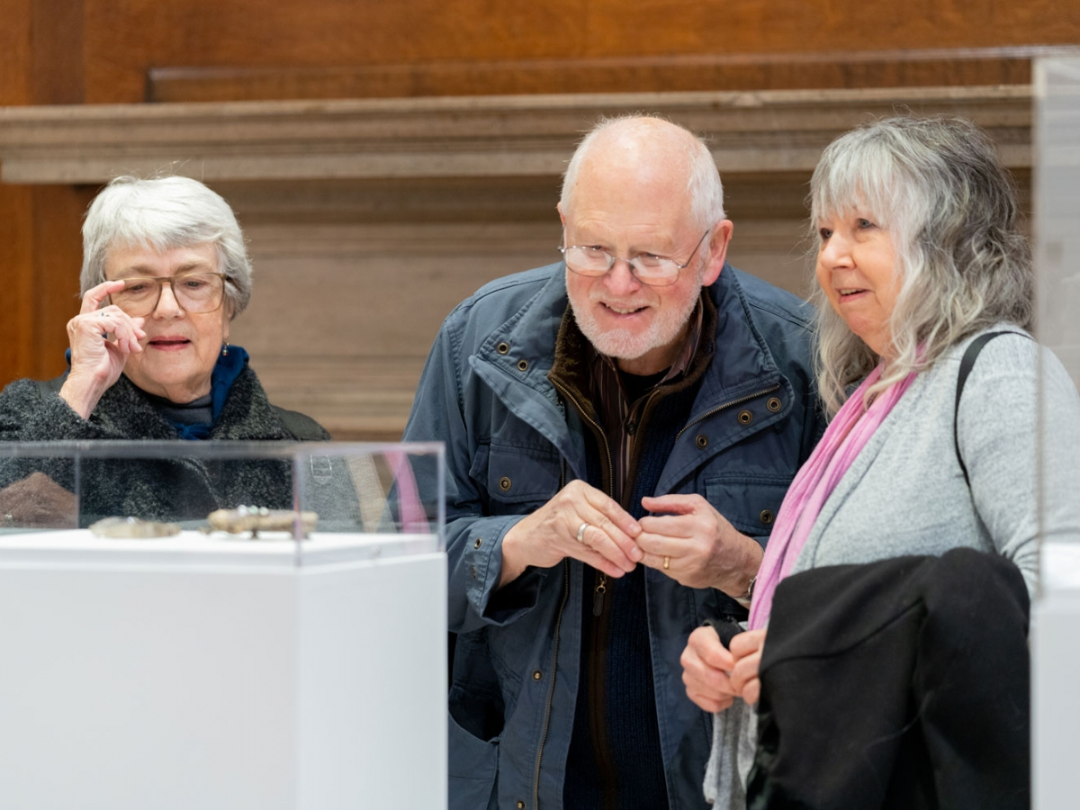 Three people looking at a piece of art in the Invisible City gallery