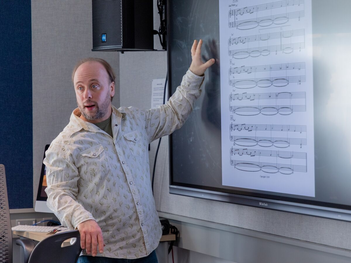 Faculty member Randy Kapralick shows an excerpt to students during class.