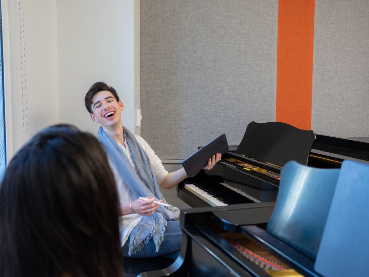 A student laughs during their private piano lesson.