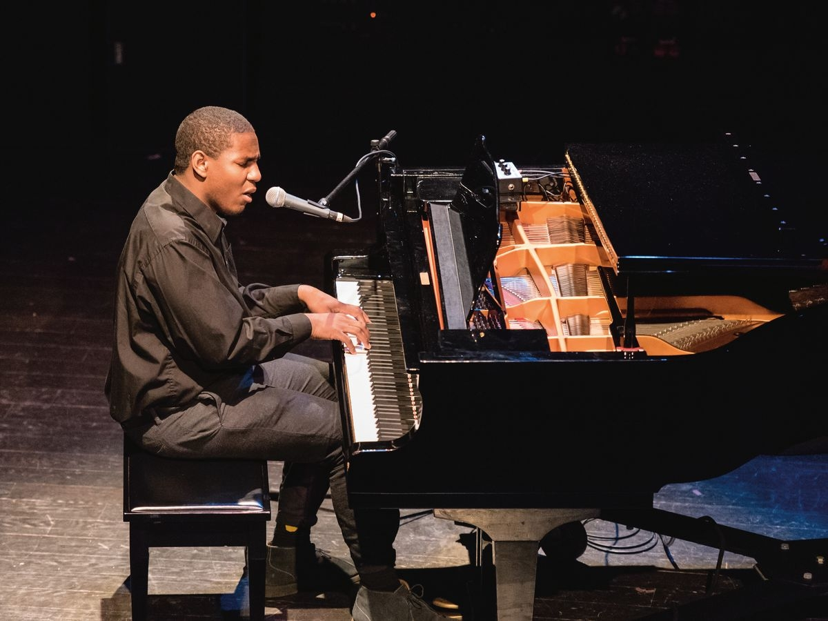 A student performs a solo on the piano while singing.