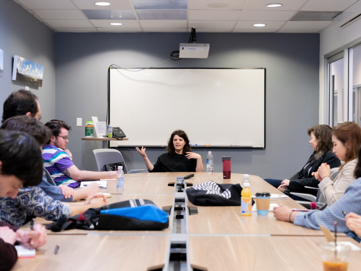 Students and faculty sit around a conference room table and learn from alum Jenn Wexler BFA '08 (WFTV).