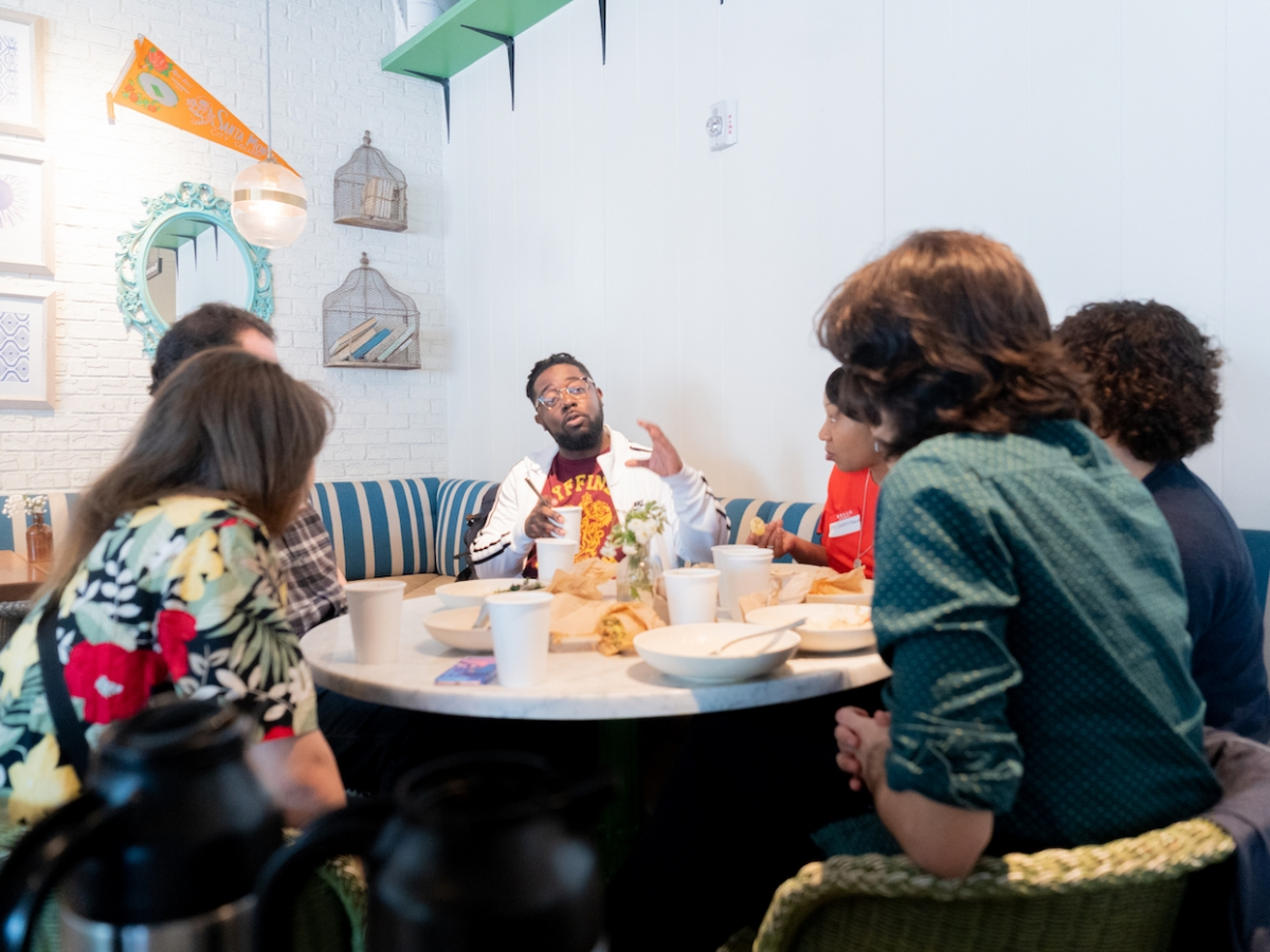 Students sit around a brunch table and meet with alum Darnell Brown BFA '10 (WFTV).
