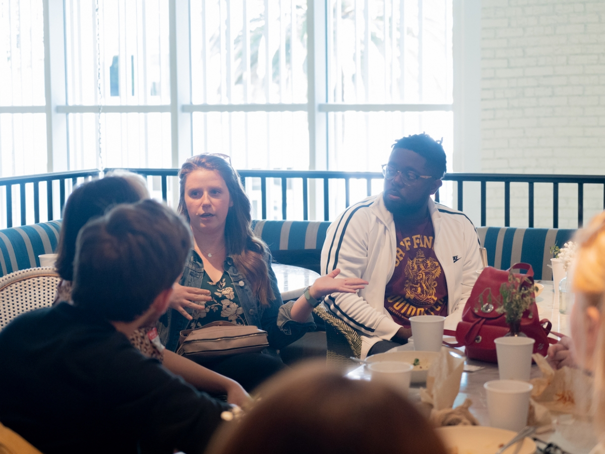 Students and faculty sit around a brunch table and speak with alumni Lauren Deacon BFA '09 (WFTV) and Darnell Brown Darnell Brown BFA '10 (WFTV).