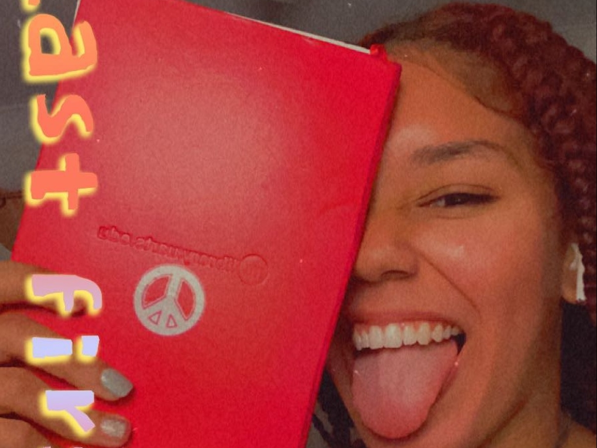 Selfie of Melanie sticking her tongue out holding a notebook