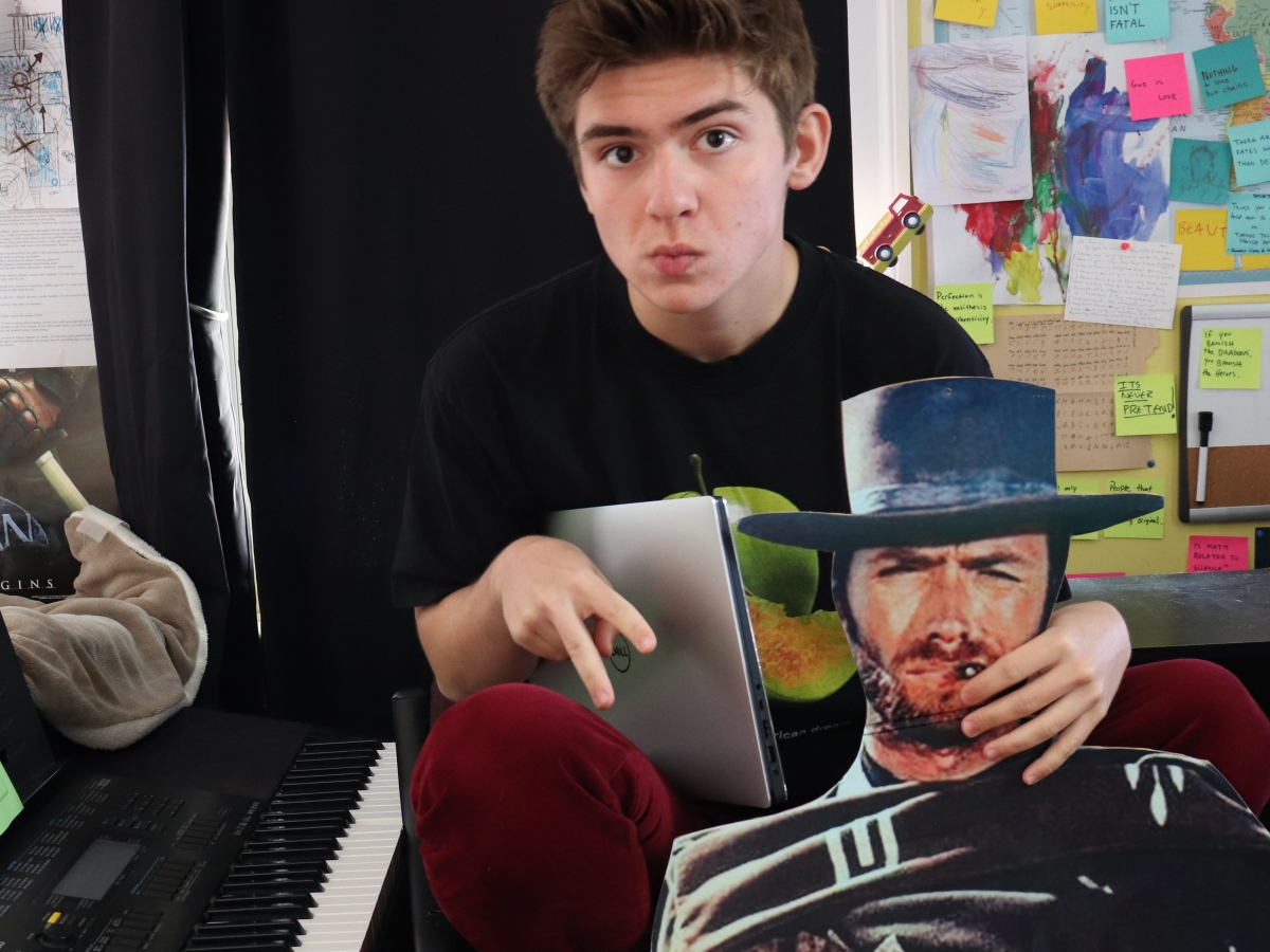 Photo of Daniel next to piano, cardboard cutout, and laptop