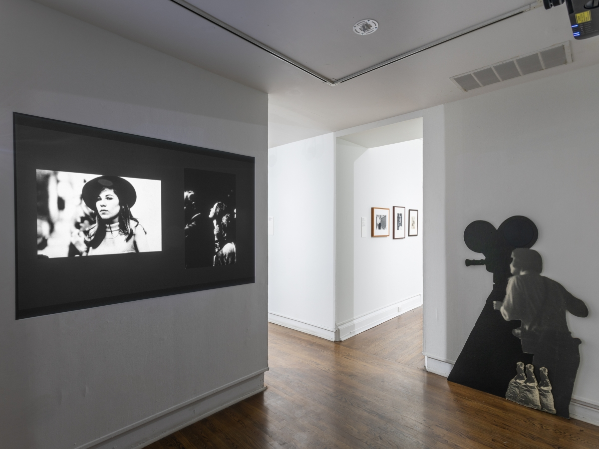 Invisible City Exhibition, Gallery D: film projection onto a dividing wall showing two still frames of people to the left and a black and white cut-out of a woman standing with a camera