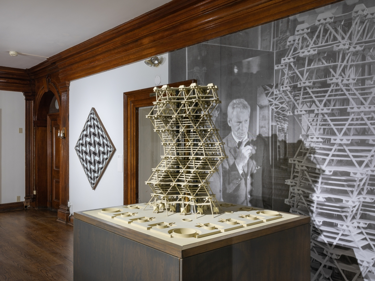 Invisible City Exhibition, 2nd Floor Landing: angled perspective of the landing, with the model of Anne Tyng's and Louis Kahn's City tower in the right foreground and a geometric painting in the left background