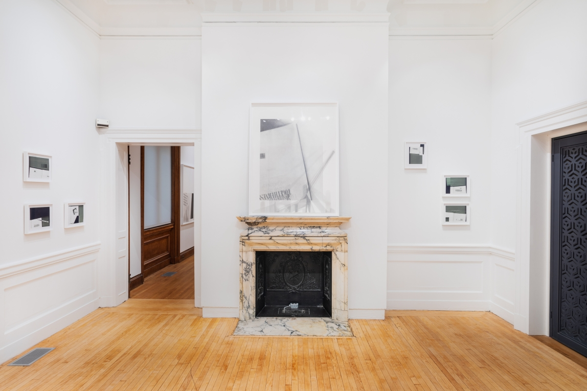 Installation shot of Nyeema Morgan's smaller framed collages hanging on walls in the left and the right of the space and a larger framed graphite drawing hangs above  in a gallery a prominent marble fireplace in the center of the photo. The gallery space features white walls and a wooden floor.