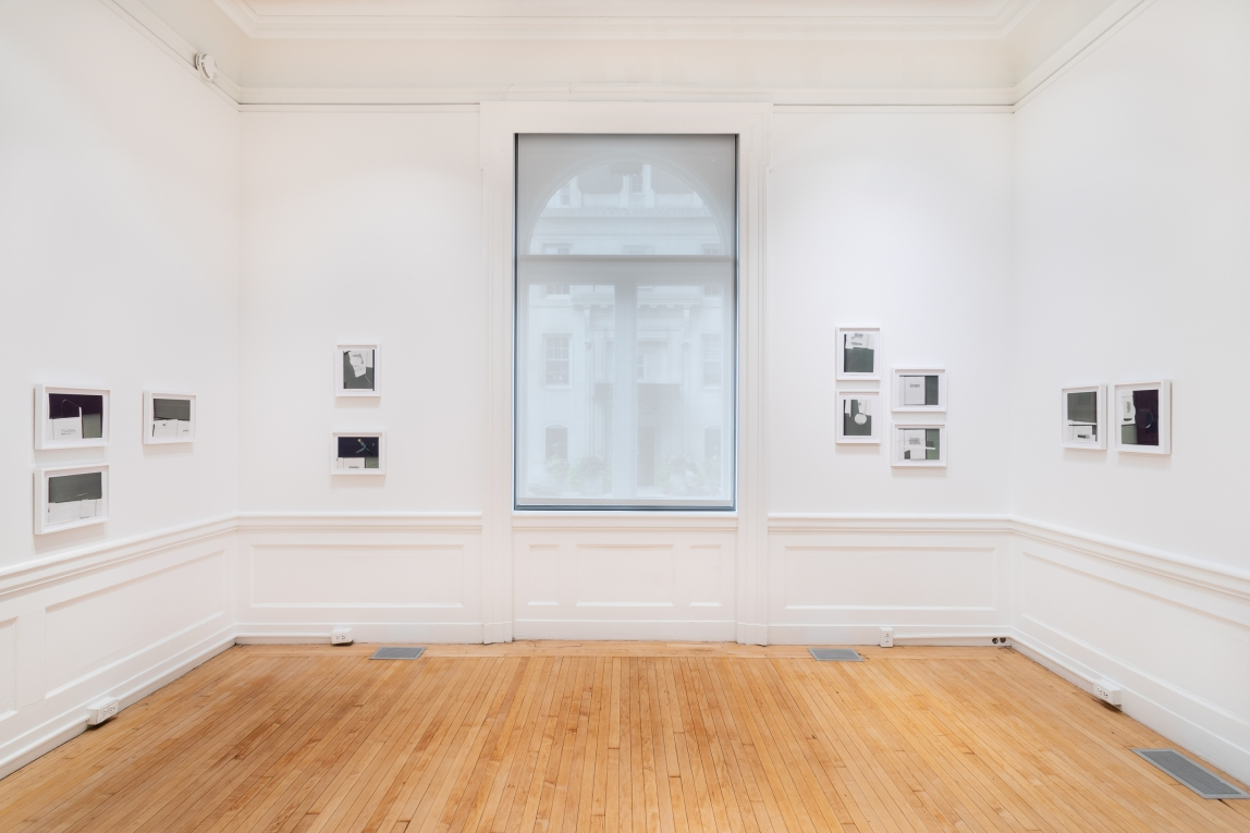 Installation shot of small greyscale framed collages on the left and right walls of a gallery space with white walls and a wooden floor. A large window in the center of the back wall is flanked by collages on the left and right of the surrounding wall space.