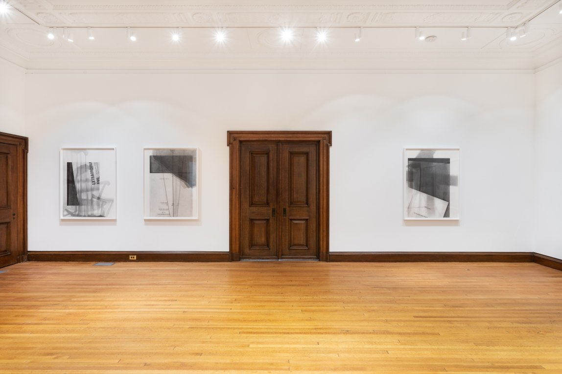 Three graphite drawings by Nyeema Morgan hang in white frames on a white wall. Two hang to the left of a large wooden door in the center of the photograph and the third hangs on the right side. Each depicts the title page of a book with some fragmented text, white space, and darker grey shadowed areas included in the compositions.