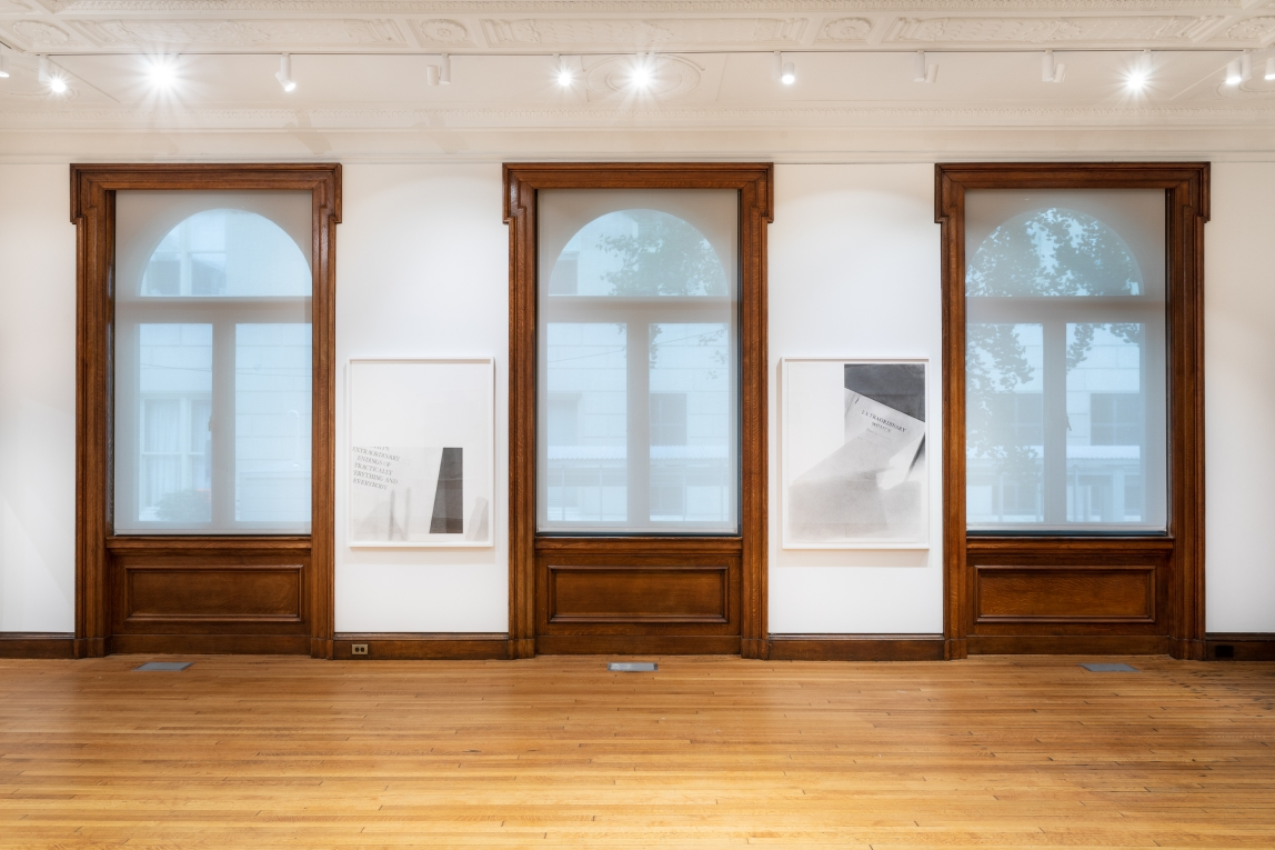 two graphite drawings by Nyeema Morgan hang in the alternating wall space between three large wooden framed windows.  in white frames on a white wall. Each depicts the title page of a book with some fragmented text, white space, and darker grey shadowed areas included in the compositions.