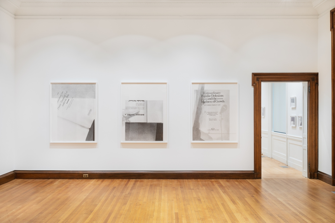 Three graphite drawings by Nyeema Morgan hang in white frames on a white wall to the left of a wide wood framed doorway. Each depicts the title page of a book with some fragmented text, white space, and darker grey shadowed areas included in the compositions.