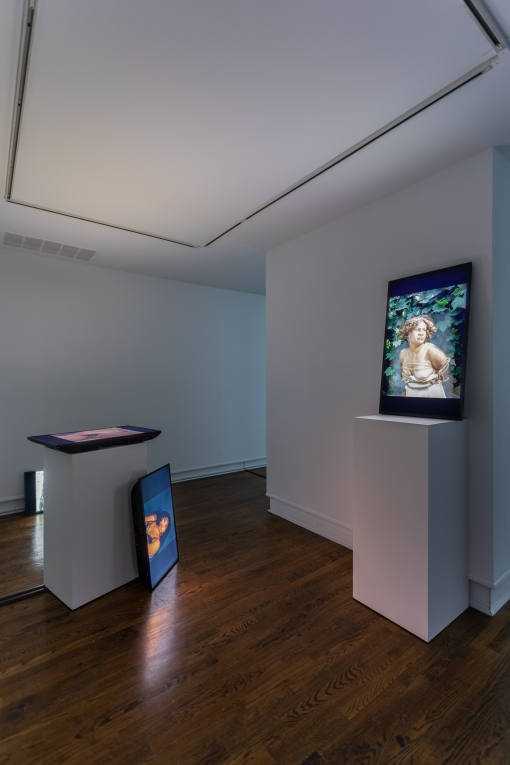 an installation shot of Abbey Williams' work in a gallery space. Three digital monitors are around the room leaning against and on top of pillars. The screens displaying stills from various videos each featuring a different female figure shown.