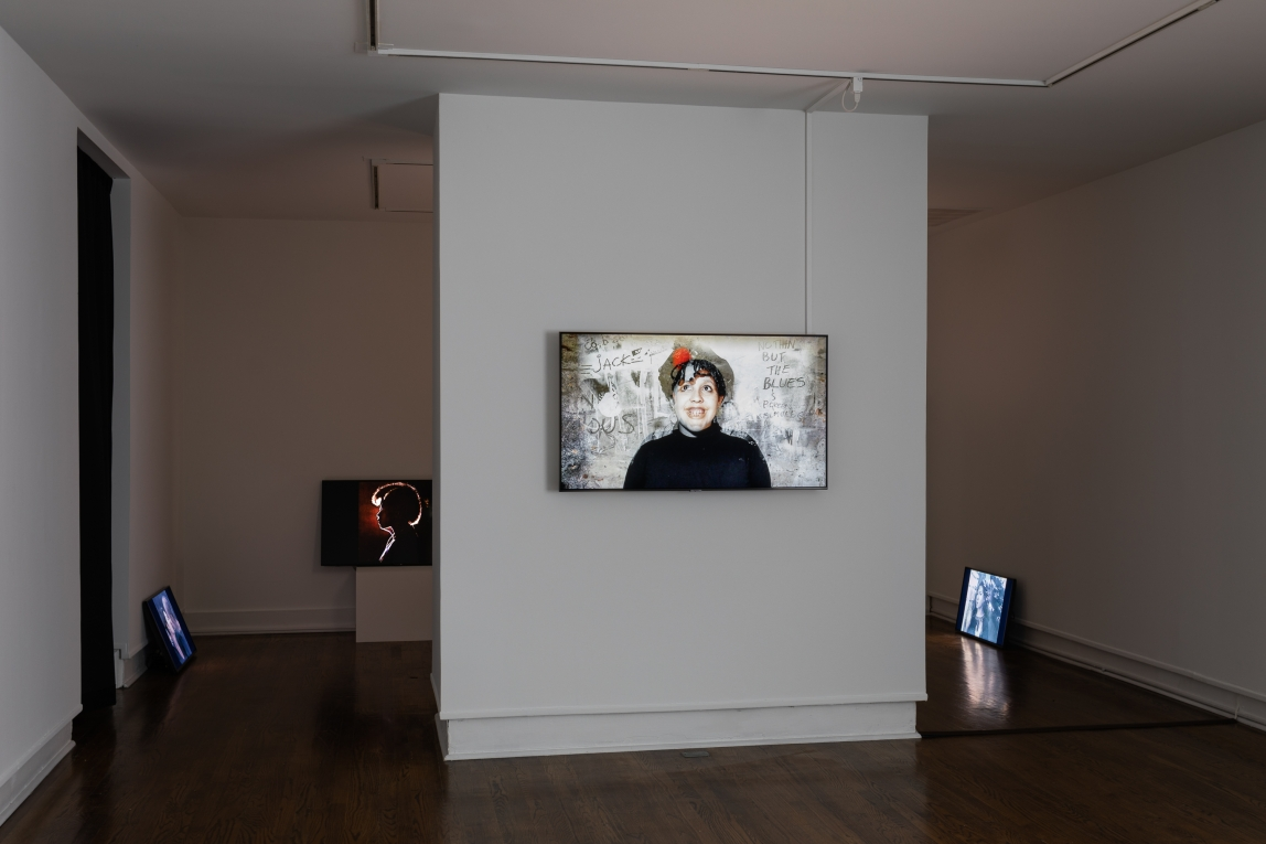 installation shot of Abbey Williams' work. Digital monitors are around the room leaning on pillars and the walls. The screens display stills from various videos each featuring a different figure shown. A monitor in the center of the image depicts a smiling figure wearing black against a grey background with text fragments visible.