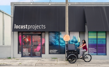 Woman riding a tricyle on the sidewalk outside of a Miami art gallery