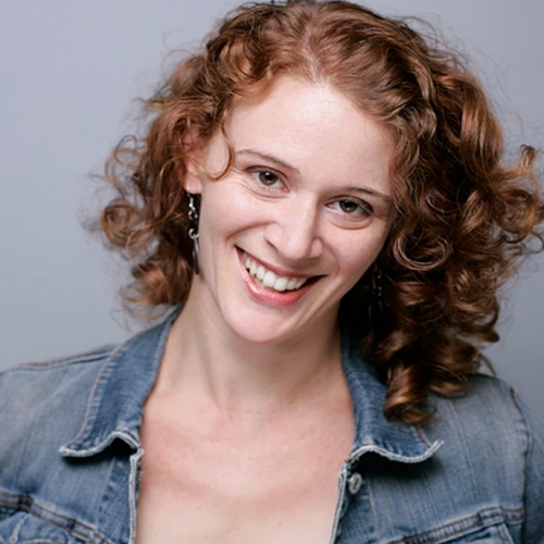 Head shot of Krista Apple Hodge smiling, red hair, purple blouse, jean jacket