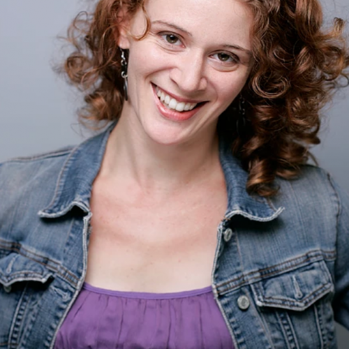 Krista Apple-Hodge headshot, red hair smiling, wearing purple blouse and jean jacket