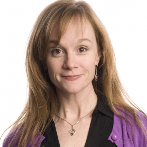 Head shot image of Jennifer Childs with red hair in black shirt and purple jacket