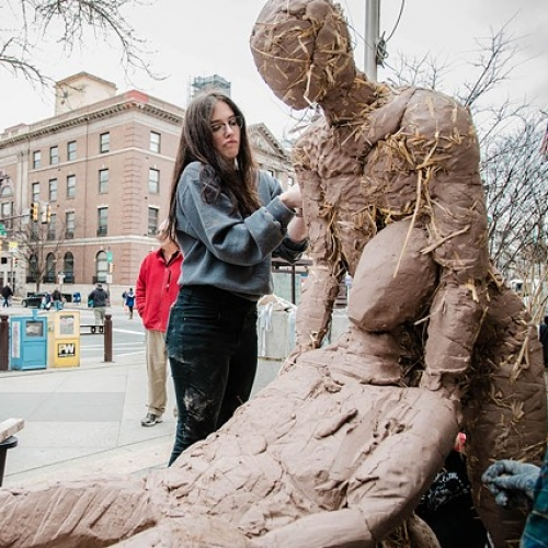 Ciara Wright sculpting a clay figure on Broad Street in Philadelphia