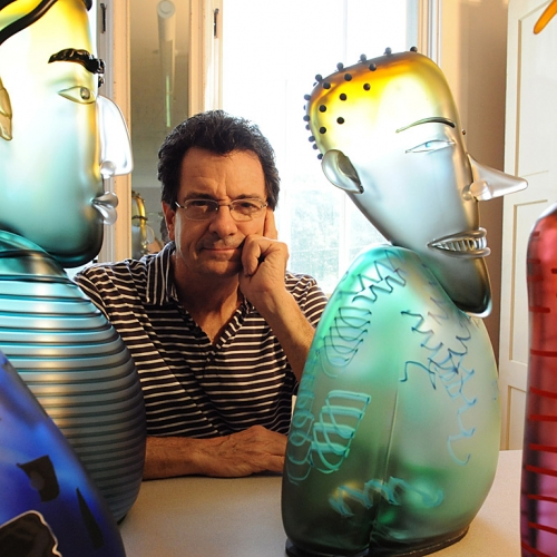Glass artist Dan Dailey with four colorful glass sculptures of people