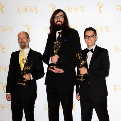 UArts alum Derek Dressler in center of two colleagues dressed in tuxedos on Emmy Awards red carpet, holding Emmy statuettes
