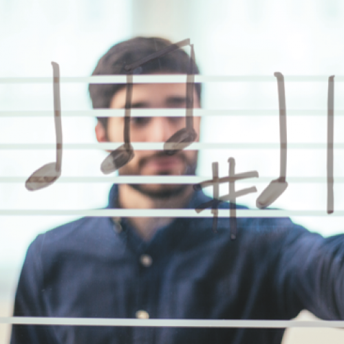 In the foreground drawn music notes, through a clear whiteboard a man in the background draws the notes.