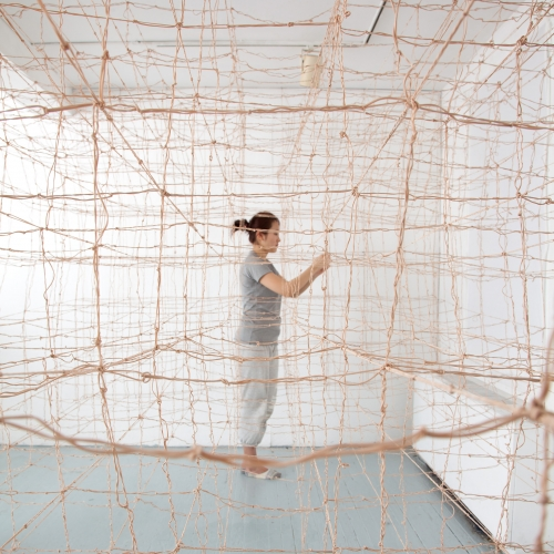 Fibers senior Qiang Gong creating room-wide netting installation