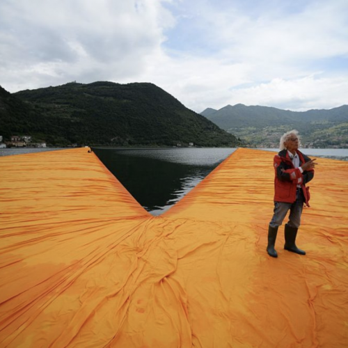 A man standing on a great orange sheet, which is floating in a lake