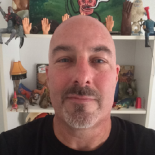 John Serpentelli head shot, bald, black t shirt, in front of bookshelf with small plastic hands and a cartoon painting